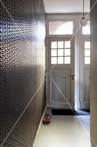Geöffnete haustür  Hauseingang, seitlich tapezierte Wand mit geometrischem Muster, im ...