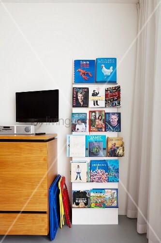 vor wand zeitungsst nder mit b chern neben sideboard aus hellem holz fernseher mit lautsprecher. Black Bedroom Furniture Sets. Home Design Ideas