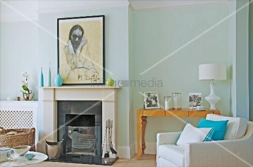 offener kamin und weisser polstersessel vor kunsthandwerklichem konsolentisch mit familienfotos. Black Bedroom Furniture Sets. Home Design Ideas