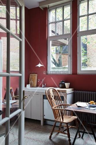 blick durch offene sprossent r auf armlehnstuhl mit hoher r ckenlehne am esstisch in schlichter. Black Bedroom Furniture Sets. Home Design Ideas