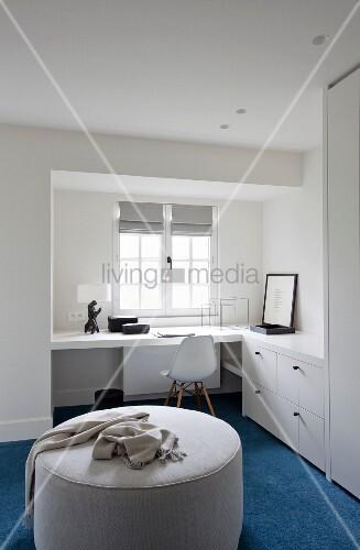 grosser heller sitzpouf auf blauem teppich im hintergrund klassikerstuhl vor arbeitsplatz. Black Bedroom Furniture Sets. Home Design Ideas