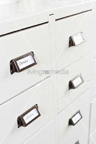 beschriftete schubladengriffe eines weiss lackierten vintage schubladenschranks bild kaufen. Black Bedroom Furniture Sets. Home Design Ideas