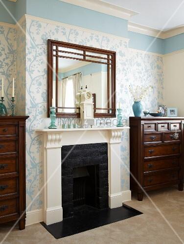 weiss umrahmter kamin und spiegel zwischen kommoden florale tapete und fries in hellblau bild. Black Bedroom Furniture Sets. Home Design Ideas