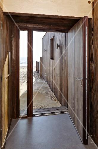 Offene haustür  Blick von Hauseingang durch offene Haustür auf Sandstrand und Meer ...