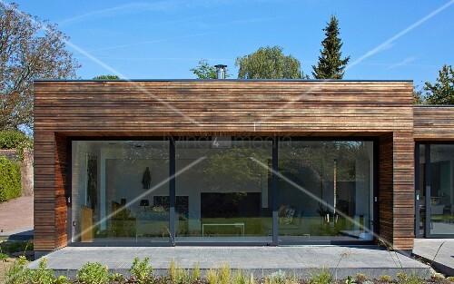 blick von garten auf zeitgen ssisches wohnhaus mit terrasse und grossformatigen glas. Black Bedroom Furniture Sets. Home Design Ideas