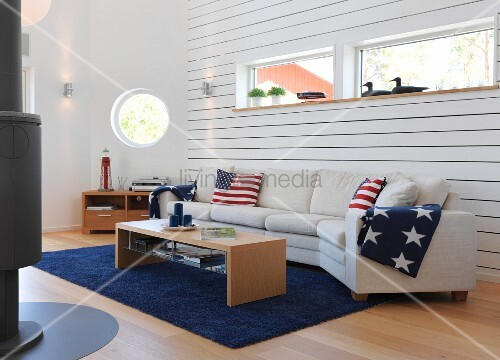 weisse sofalandschaft mit stars and stripes deko vor holzverschalter wand mit fensterband und. Black Bedroom Furniture Sets. Home Design Ideas