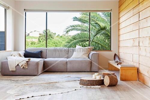 panoramafenster gema 1 4 tliche wohnzimmerecke mit polstersofa am auf holzboden tierhaut baumstamm scheiben als bodentisch seitlich bank an holzverkleideter einbauen