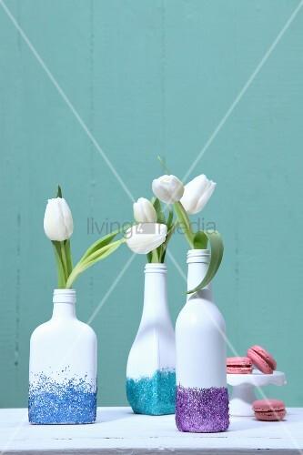 weiss bemalte flaschen mit buntem glitzer als vasen mit weissen tulpen vor t rkisfarbener wand. Black Bedroom Furniture Sets. Home Design Ideas