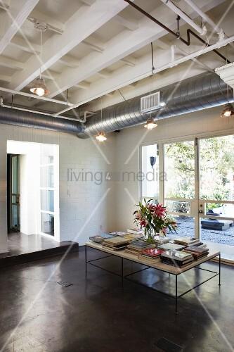 tisch mit b cherstapel und blumenstrauss in minimalistischem ambiente mit betonboden bild. Black Bedroom Furniture Sets. Home Design Ideas