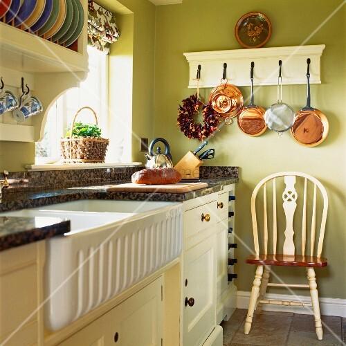Weisse Küchenzeile in grün getönter Küche im Landhausstil mit ...