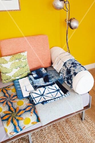 Batiktücher auf Tagesliege mit Polstern vor gelber Wand ...