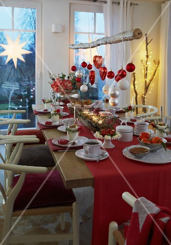 festlich gedeckter weihnachtstisch in rot und weiss dar ber abgeh ngter ast mit. Black Bedroom Furniture Sets. Home Design Ideas