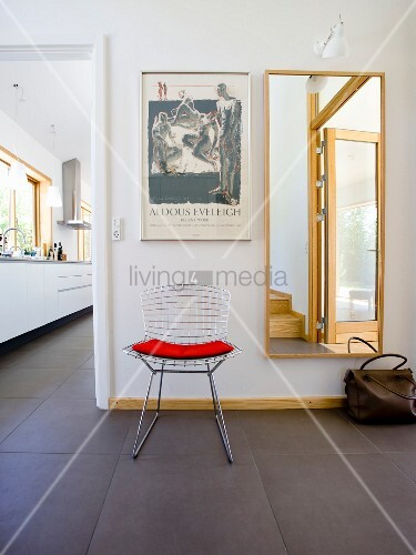 im gangbereich klassikerstuhl aus metallgitter mit rotem kissen neben wandspiegel seitlich. Black Bedroom Furniture Sets. Home Design Ideas
