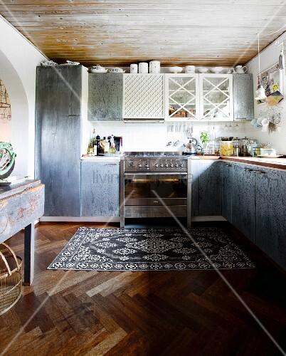 einbauk che mit grauen schrankoberfl chen in schlichter k che mit vintage teppich auf. Black Bedroom Furniture Sets. Home Design Ideas