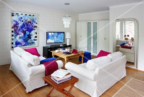 Weiss möbliertes Wohnzimmer mit starken Farbakzenten in Magenta ...