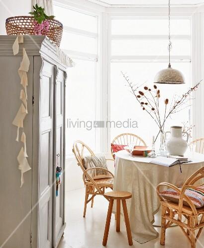 esszimmer mit rattanst hlen und orientalischer silberner h ngeleuchte landhausschrank im. Black Bedroom Furniture Sets. Home Design Ideas