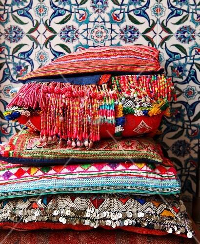 bunt gewebte kissen mit perlenfransen und pailletten vor floral gemusterten marokkanischen. Black Bedroom Furniture Sets. Home Design Ideas