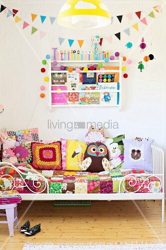bett mit weissem gittergestell patchwork tagesdecke und bunt gemusterte kissen vor wand mit. Black Bedroom Furniture Sets. Home Design Ideas
