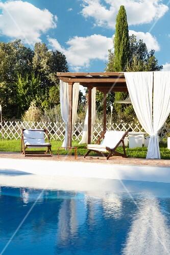 holzpergola mit wei en vorh ngen und holzliegest hle mit wei en polstern im sommerlichen garten. Black Bedroom Furniture Sets. Home Design Ideas