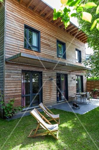 liegest hle im garten vor zeitgen ssischem holzhaus kleine terrasse mit sonnenschutz bild. Black Bedroom Furniture Sets. Home Design Ideas