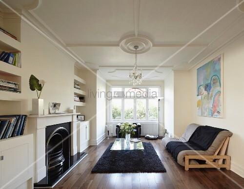 einfaches futonsofa und moderner glastisch in altbauwohnraum mit stuckdecke offener kamin und. Black Bedroom Furniture Sets. Home Design Ideas