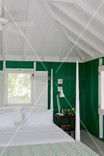 bl tenweiss bezogenes bett mit eckpfosten unter einer zeltdachkonstruktion dahinter ein fenster. Black Bedroom Furniture Sets. Home Design Ideas