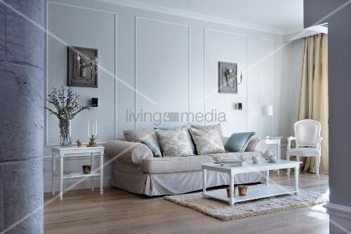 elegantes sofa und weisse antikisierende m bel vor lichtgrauer wand mit stuckrahmen und leuchter. Black Bedroom Furniture Sets. Home Design Ideas