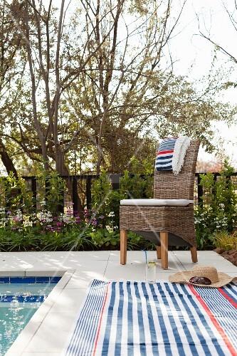 gestreifte handt cher auf rattanstuhl und gefliestem poolrand im garten bild kaufen living4media. Black Bedroom Furniture Sets. Home Design Ideas