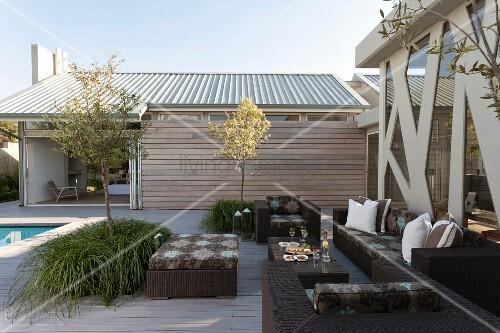 Grosszügige Terrasse mit modernen, dunklen Rattan Outdoor ...