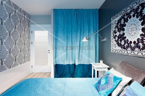wandteppich ber doppelbett mit hellblauen textilien und zweifarbig blauer vorhang vor einer. Black Bedroom Furniture Sets. Home Design Ideas