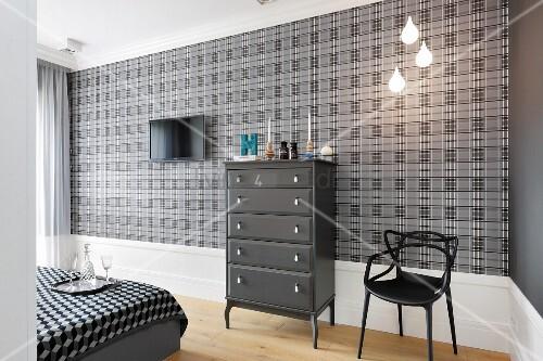 Dunkelgraue kommode und schwarzer stuhl vor grau schwarzem tapetenmuster im textillook in - Tapetenmuster schlafzimmer ...