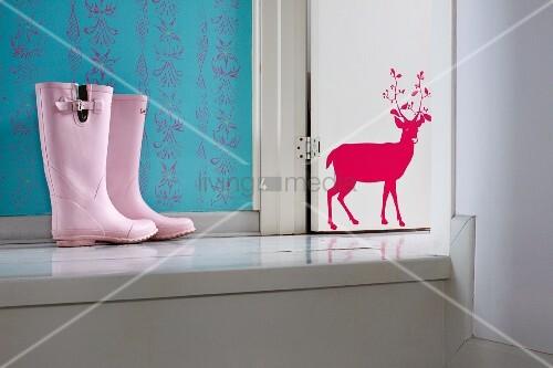 rosa kinder gummistiefel auf podest weisslackierte holzt r mit rotem hirschmotiv bild kaufen. Black Bedroom Furniture Sets. Home Design Ideas
