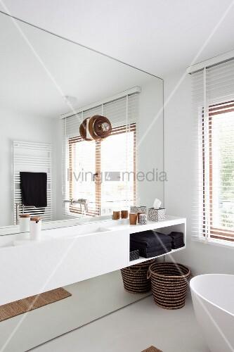 weisser waschtisch vor vollfl chiger spiegelwand im. Black Bedroom Furniture Sets. Home Design Ideas