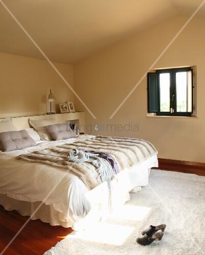 doppelbett mit fell tagesdecke und weisse bettw sche in. Black Bedroom Furniture Sets. Home Design Ideas