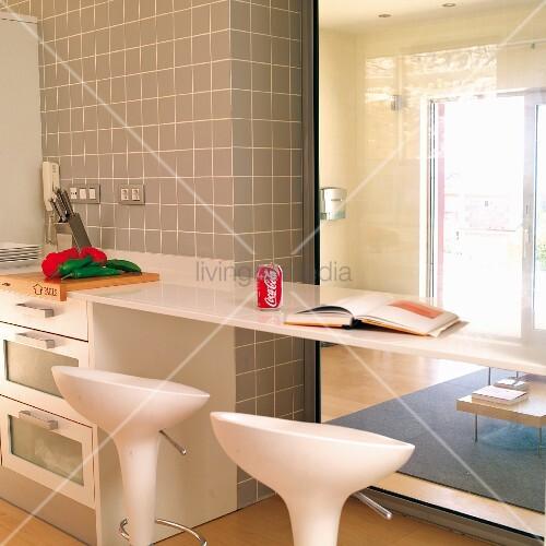k chenzeile mit verl ngerter thekenplatte und weisse barhocker vor glasscheibe mit blick in. Black Bedroom Furniture Sets. Home Design Ideas
