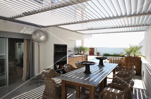 Rattanst hle um holztisch auf mit sonnenschutzlamellen berdachter terrasse bild kaufen - Holztisch terrasse ...