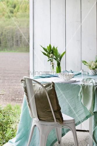 tisch mit pastellgr ner tischdecke maigl ckchen und gedeck weisser stuhl mit kissen bild. Black Bedroom Furniture Sets. Home Design Ideas