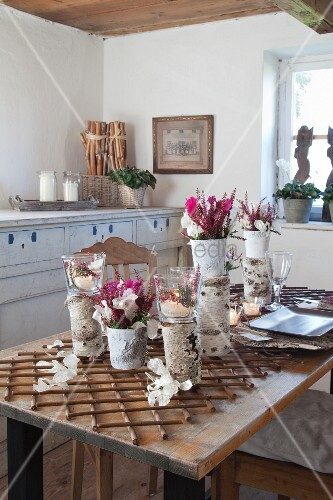 mit naturmaterialien dekorierte vasen und blumengestecke auf rustikalem tisch in b uerlichem. Black Bedroom Furniture Sets. Home Design Ideas