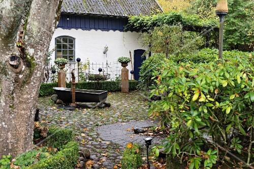 Vintage Garten vintage zinc bathtub on pebble cobbled terrace in garden of white