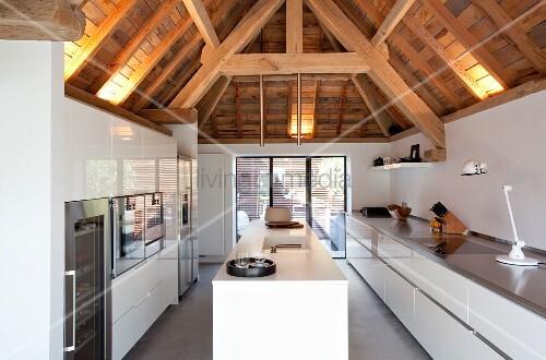 wei e hochglanz designerk che unter rustikaler holzbalkenkonstruktion mit indirekter beleuchtung. Black Bedroom Furniture Sets. Home Design Ideas
