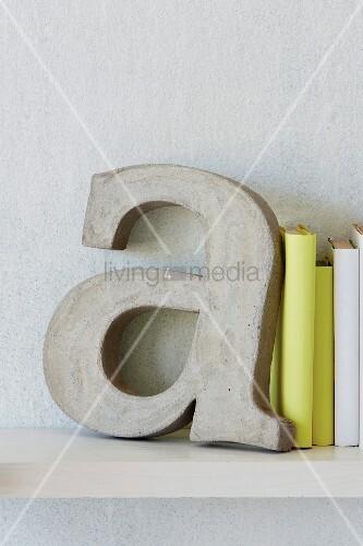deko buchstabe als buchst tze aus beton neben gelb eingebundenen b chern bild kaufen. Black Bedroom Furniture Sets. Home Design Ideas
