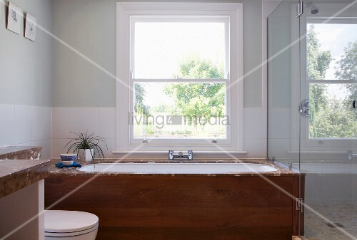 Dusche Glaswand Badewanne : Badewanne mit Holzfront vor Fenster, seitlich Glaswand vor Dusche