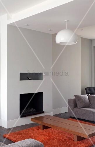 schlichter bodentisch auf rostrotem teppich vor offenem kamin in modernem wohnzimmer bild. Black Bedroom Furniture Sets. Home Design Ideas