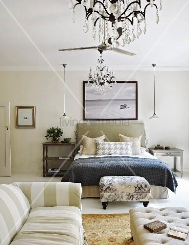 mustermix im eleganten schlafzimmer mit sofa und polsterhocker vor dem bett bild kaufen. Black Bedroom Furniture Sets. Home Design Ideas