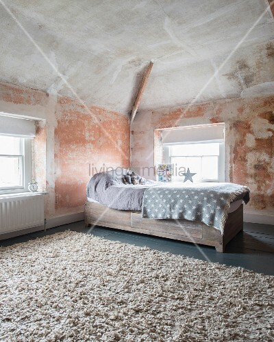 kinderbett mit bettschublade und hellgrauem plaid in puristisch renoviertem dachraum mit wand. Black Bedroom Furniture Sets. Home Design Ideas