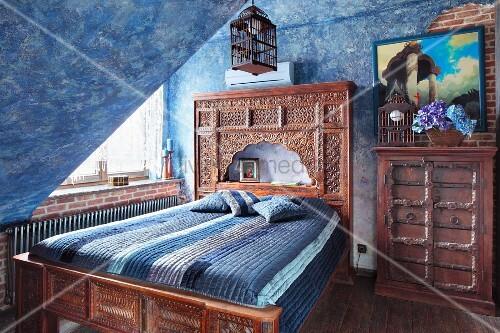 bett mit geschnitztem holzrahmen und kopfteil in orientalischem stil in dachzimmer an wand. Black Bedroom Furniture Sets. Home Design Ideas