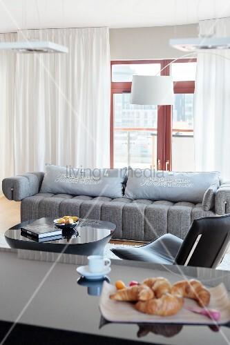 designerlampen ber grauer couch mit kissen in elegantem wohnzimmer im vordergrund h rnchen auf. Black Bedroom Furniture Sets. Home Design Ideas