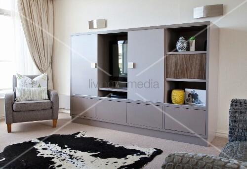 schwarz weisses tierfell vor modernem grauem schrank teilweise mit ffnungen in wohnzimmer. Black Bedroom Furniture Sets. Home Design Ideas