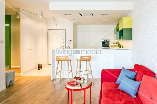 rotes sofa und weisse einbauk che mit fr hst ckstheke in offenem wohnbereich bild kaufen. Black Bedroom Furniture Sets. Home Design Ideas