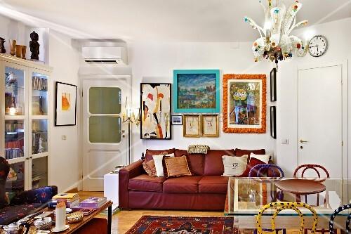 farbenfrohes wohnzimmer mit gem tlichem rotem ledersofa verschiedenen bildern und rahmen in. Black Bedroom Furniture Sets. Home Design Ideas
